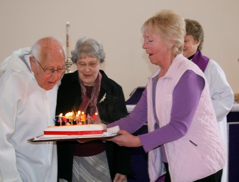 Harold Barber blows out the candles on his birthday cake. Next to Harold is wife Rae, Penny Ellis os presenting the cake, while the Rev'd Stefanie Hodges, looks on.