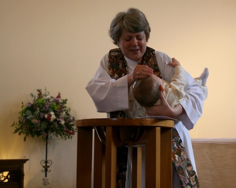 The Rev'd Stefanie Hodges baptises Alexander.